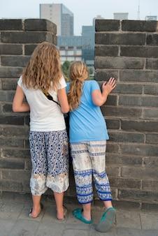 Opinião traseira os adolescentes que olham para baixo de xian city wall, xi'an, shaanxi, china.