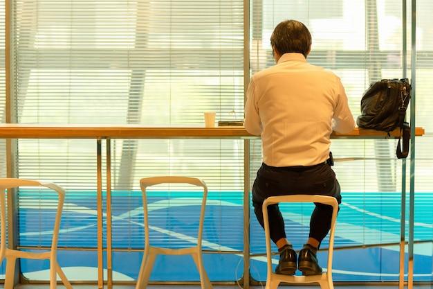 Opinião traseira os homens de negócios que sentam-se no contador de serviço na partida de espera do voo da sala de estar do aeroporto.