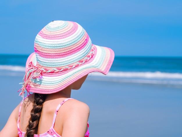 Opinião traseira uma menina adolescente que aprecia a vista na praia tropical.
