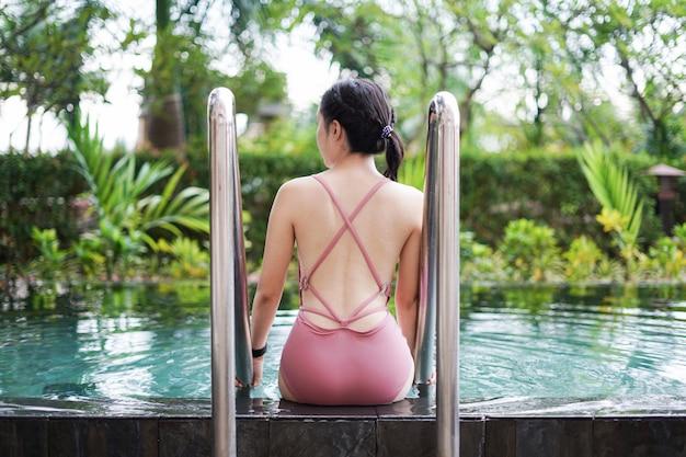 Opinião traseira uma mulher que relaxa na piscina.