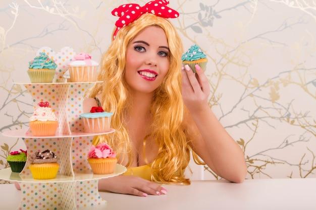 Opinião uma menina loura do pinup bonito com queques coloridos em uma tabela.