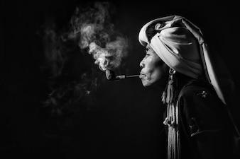 Ópio de fumo da mulher tribal de Karen com uma tubulação perto de Chiangmai, Tailândia.