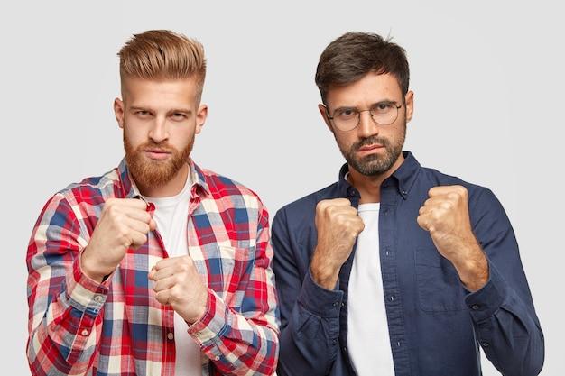 Oponentes sérios mostram os punhos, prontos para a luta, têm expressões faciais rígidas, defesa própria