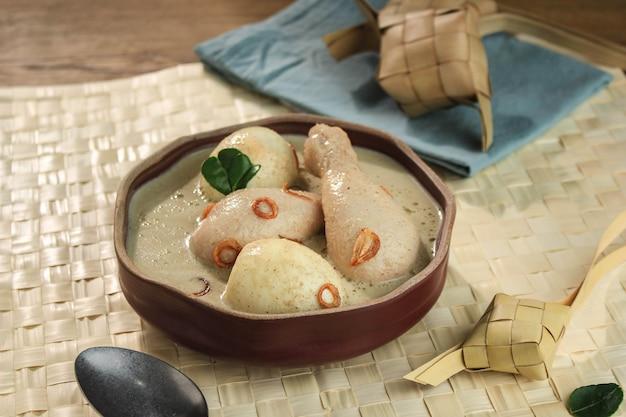 Opor ayam telur, frango e ovo cozido cozido em leite de coco da indonésia, servido com lontong ou ketupat e sambal. prato popular do líbano ou eid al-fitr