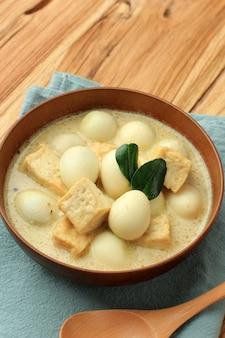 Opor tahu telur puyuh ou curry indonésio com tofu e ovo de codorniz, servido em tigela marrom