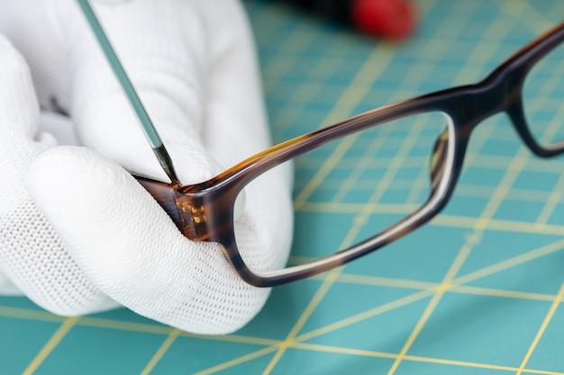 Óptico com as mãos nas luvas, consertando óculos com uma ferramenta.