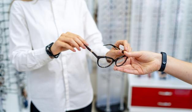 Óptico, optometrista, oculista ou oftalmologista segurando óculos e óculos com lentes novas.