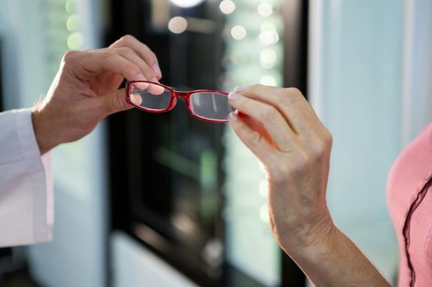 Optometrista dando óculos ao cliente na loja de óptica