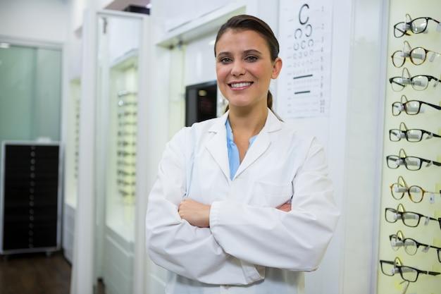 Optometrista de pé com os braços cruzados na loja de óptica