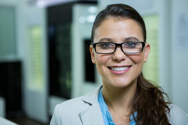 Optometrista em óculos sorrindo na loja de óptica