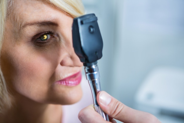 Optometrista examinando paciente do sexo feminino através do oftalmoscópio