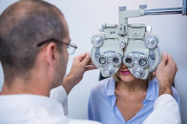 Optometrista examinando paciente do sexo feminino em phoropter