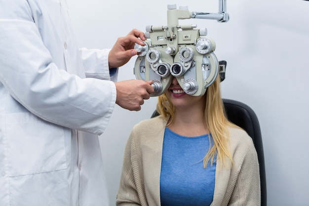 Optometrista examinando paciente do sexo feminino no phoropter