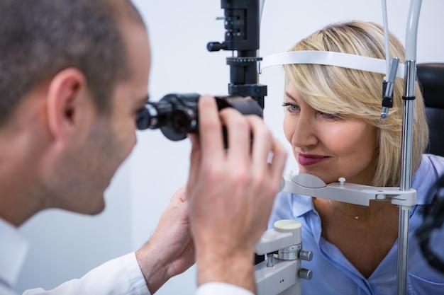 Optometrista examinar paciente do sexo feminino na lâmpada de fenda