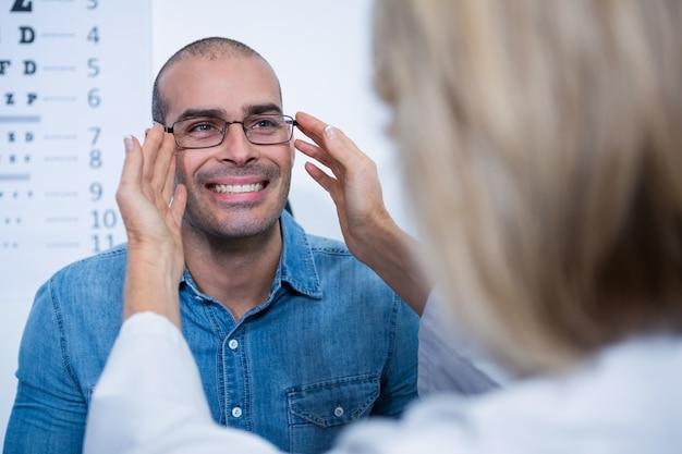 Optometrista fêmea que prescreve espetáculos ao paciente