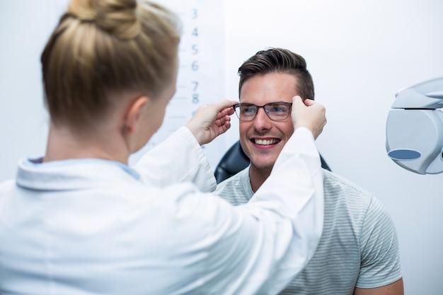 Optometrista fêmea que prescreve óculos ao paciente