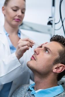 Optometrista feminina colocando colírio nos olhos do paciente