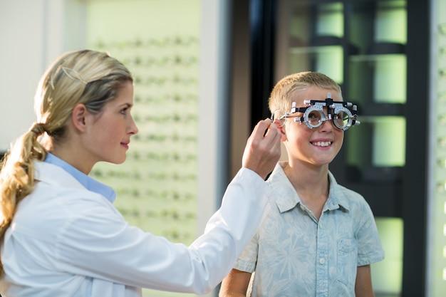 Optometrista feminina examinar paciente jovem com phoropter