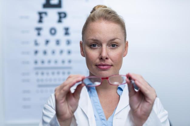 Optometrista feminina segurando óculos