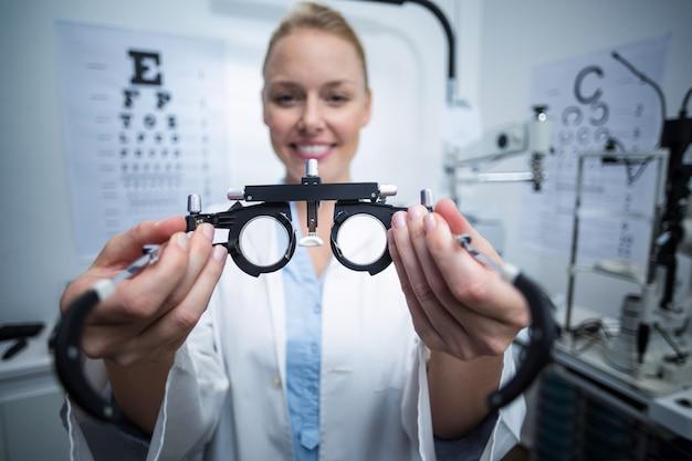 Optometrista feminina sorridente segurando messbrille