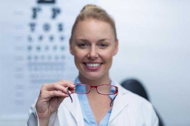 Optometrista feminina sorridente segurando óculos