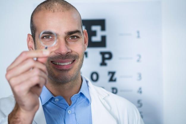 Optometrista masculina olhando através de lupa