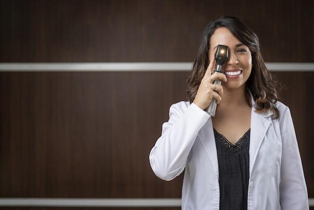 Optometrista profissional sorrindo e segurando um equipamento para exame oftalmológico