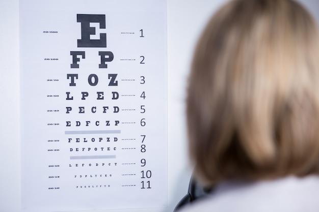 Optometrista que olha a carta de olho