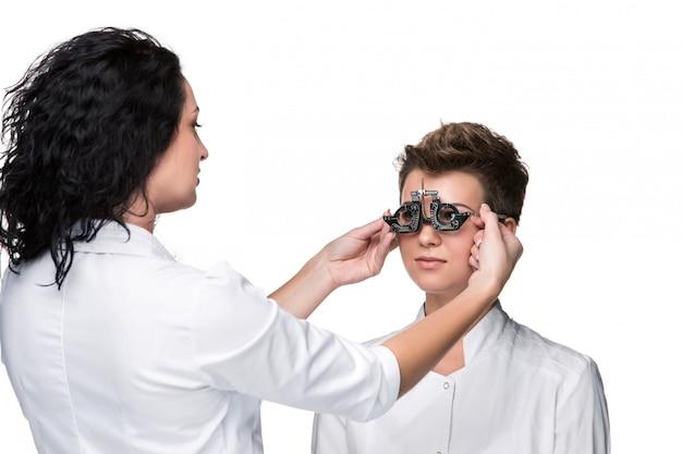 Optometrista segurando um óculos de teste do olho e dando ao exame de mulher jovem