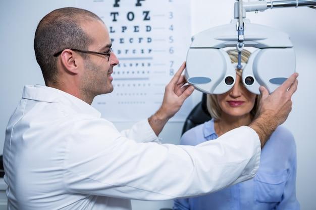 Optometrista sorridente, examinando o paciente do sexo feminino em phoropter