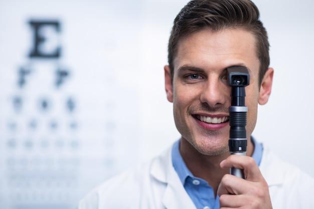 Optometrista sorridente, olhando através do oftalmoscópio