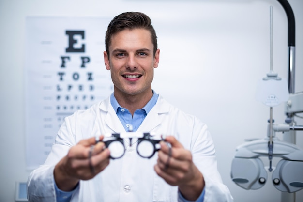 Optometrista sorridente segurando messbrille
