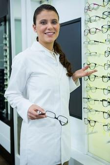 Optometrista sorridente segurando óculos na loja de óptica