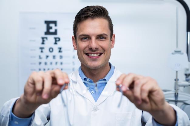 Optometrista sorridente segurando óculos