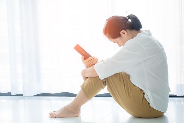 Oração da crise da vida cristã a deus. mulher ore para que deus abençoe e deseje ter uma vida melhor. mulher com as mãos orando a deus com a bíblia. implorando por perdão e acreditando na bondade.