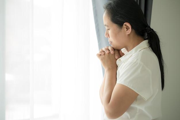 Oração da crise da vida cristã a deus. mulher ore para que deus abençoe e deseje ter uma vida melhor. mulher com as mãos orando a deus. implorando por perdão e acreditando na bondade.