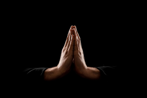 Oração do close up das mãos do homem isolada no fundo preto.