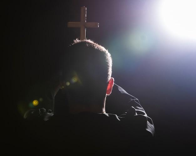Oração segurando cruz na luz da lua