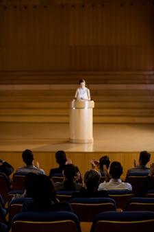 Orador aplaudindo o público após a apresentação da conferência