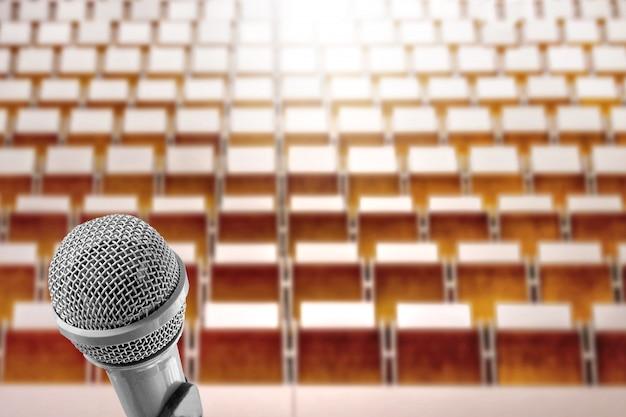 Orador da voz do microfone sobre a foto do borrão da sala de seminário vazia, salão de leitura.
