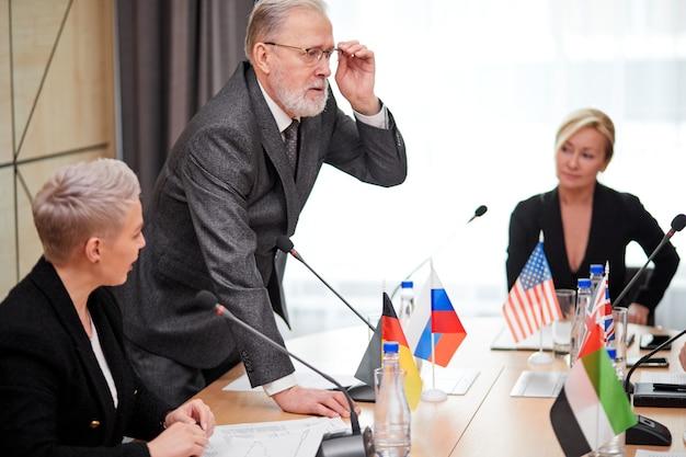 Orador sênior do sexo masculino confiante em um elegante terno cinza explicando sua opinião aos sócios e outros executivos em reunião multiétnica no escritório, usando microfones para fazer um discurso