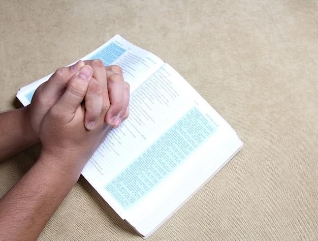 Orando com a bíblia em casa.