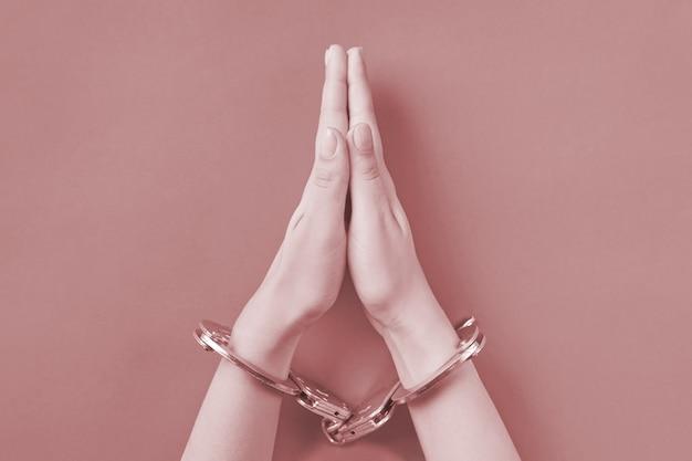Orando com as mãos algemadas. conceito de prisão perpétua. privação de liberdade e prisão dos perpetradores.