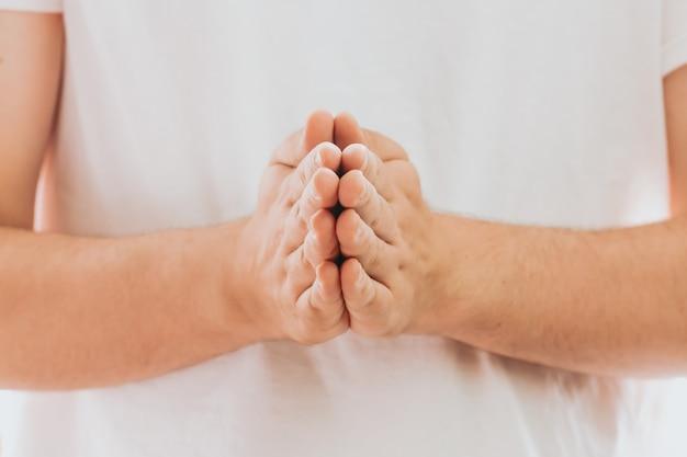 Orando com as mãos com fé na religião e crença em deus em fundo escuro. poder de esperança ou amor e devoção. posição de oração