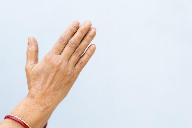 Orando com as mãos de uma pessoa em um fundo cinza