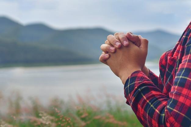 Orando com as mãos do jovem