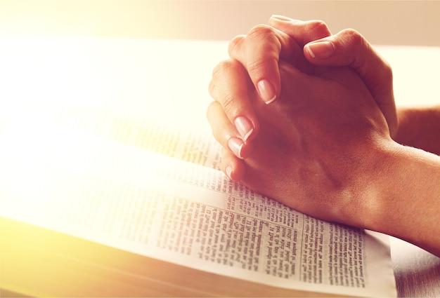 Orando com as mãos em uma bíblia aberta