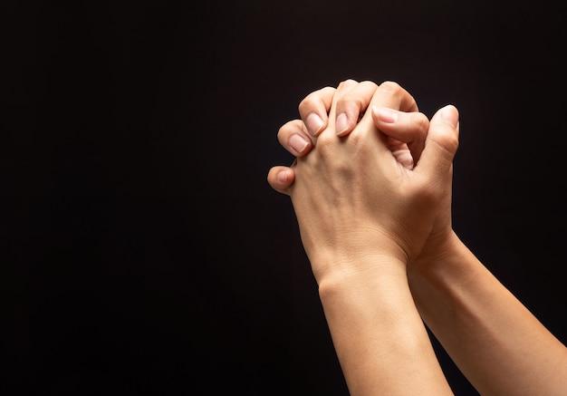 Orando com as mãos no fundo escuro, com fé na religião e crença em deus.
