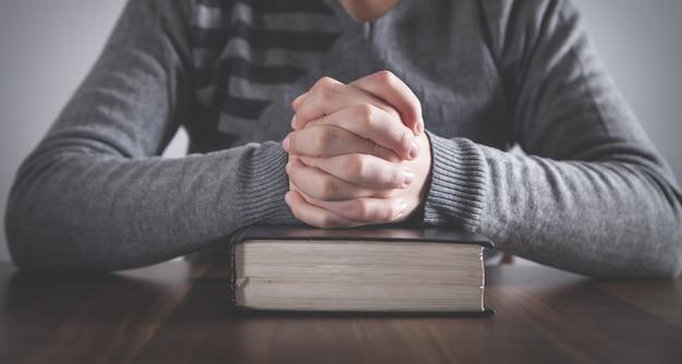 Orando humano com a bíblia. conceito de religião