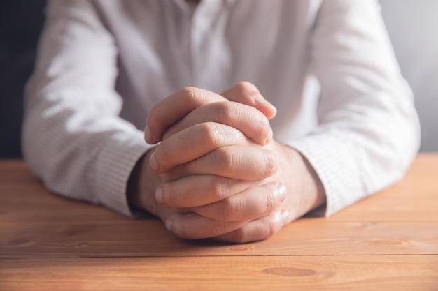 Orando na mesa de madeira.